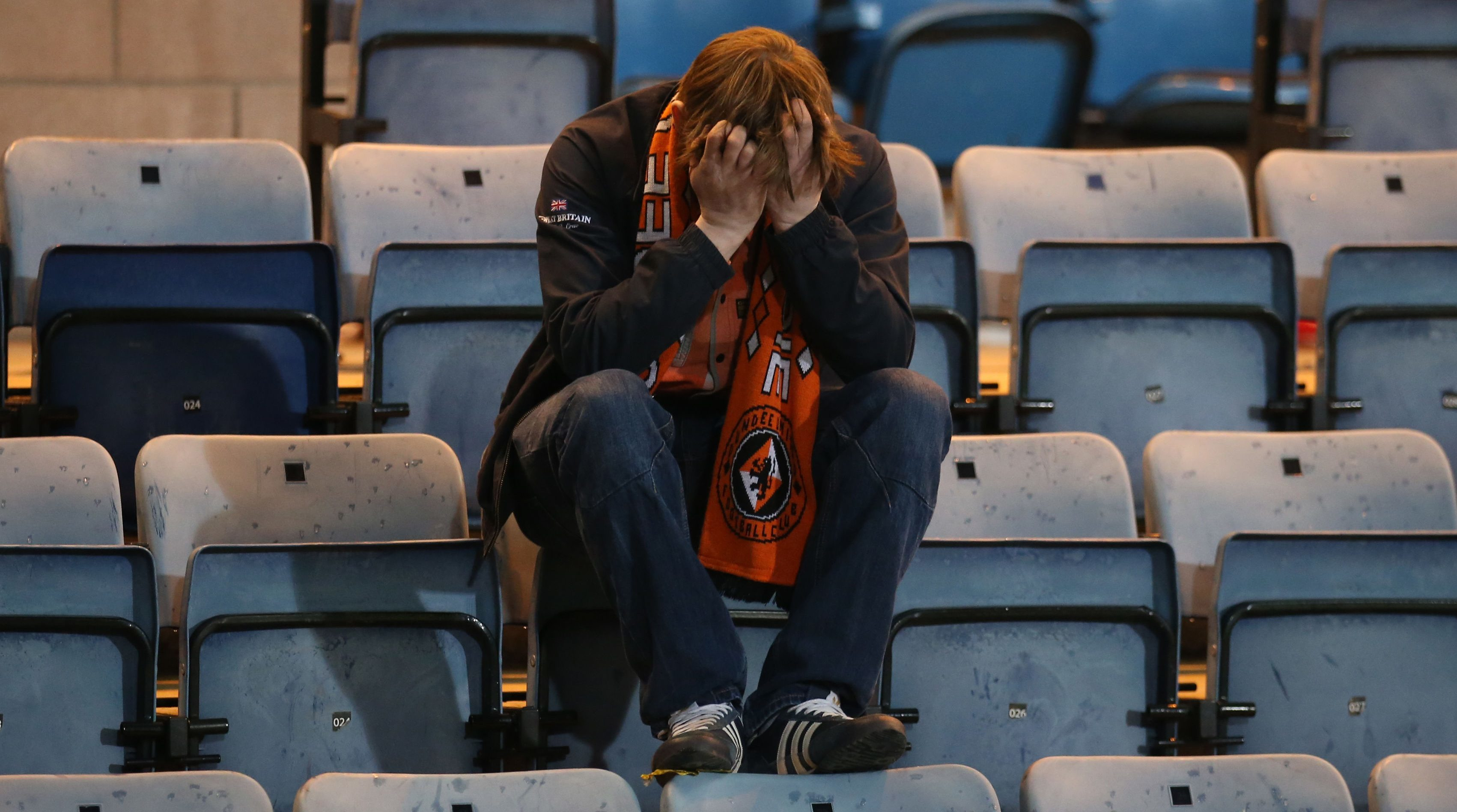 A Dundee United fan appears dejected after his side is relegated at the end of the Ladbrokes Scottish Premiership match at Dens Park.