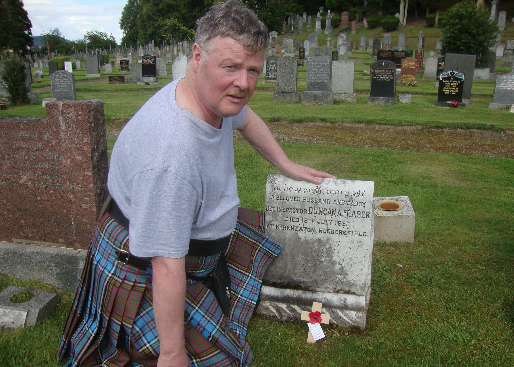 Mr Anderson pictured at the grave of Detective Inspector Duncan Fraser.