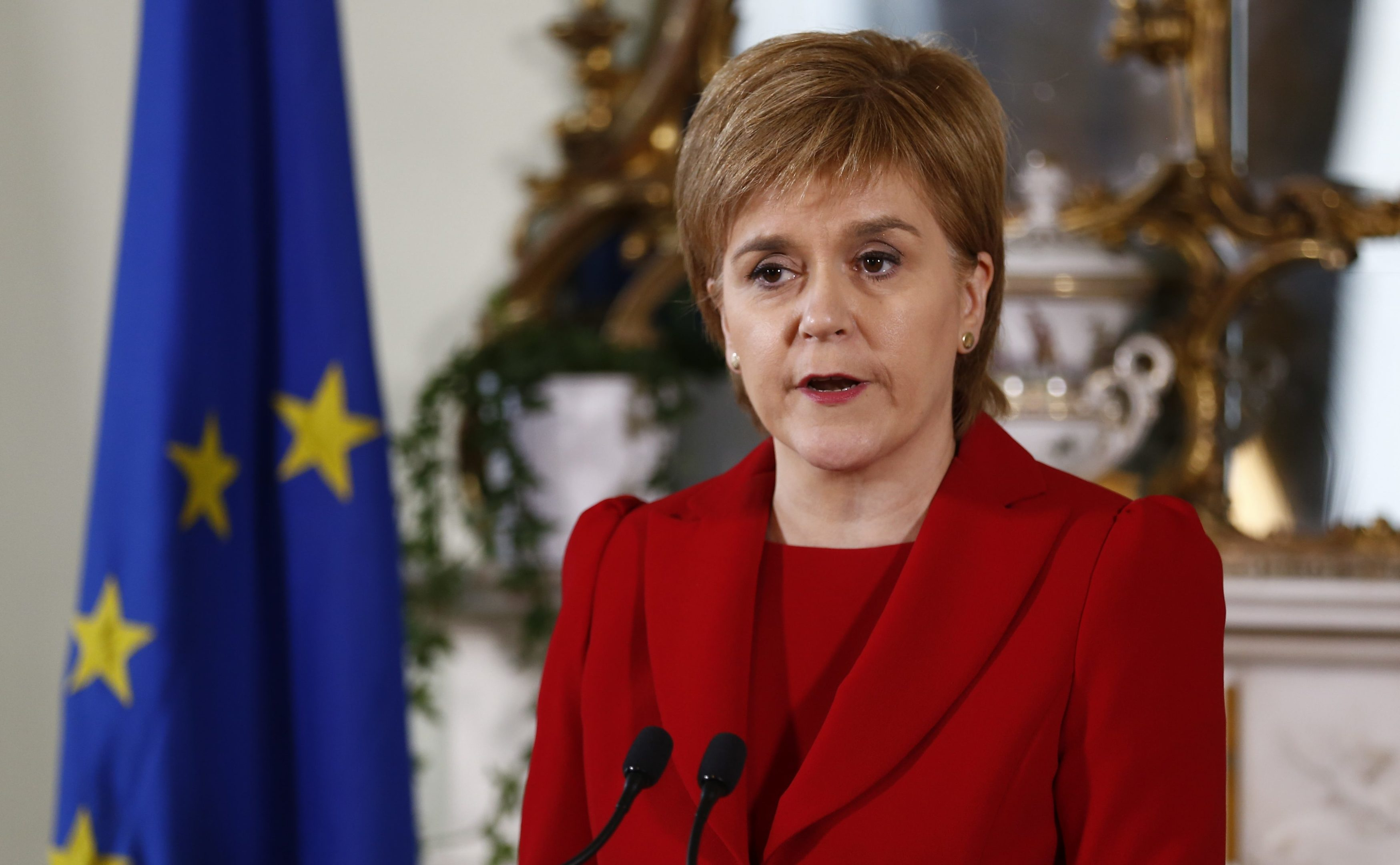 Nicola Sturgeon announces her reaction to Brexit, flanked by EU and Saltire flags.