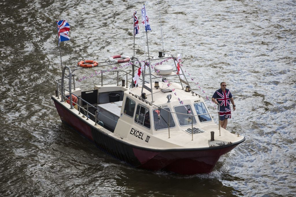 A man wearing a Union Jack shirt and shorts stands on board a boat from the 'Fishing for Leave' campaign.
