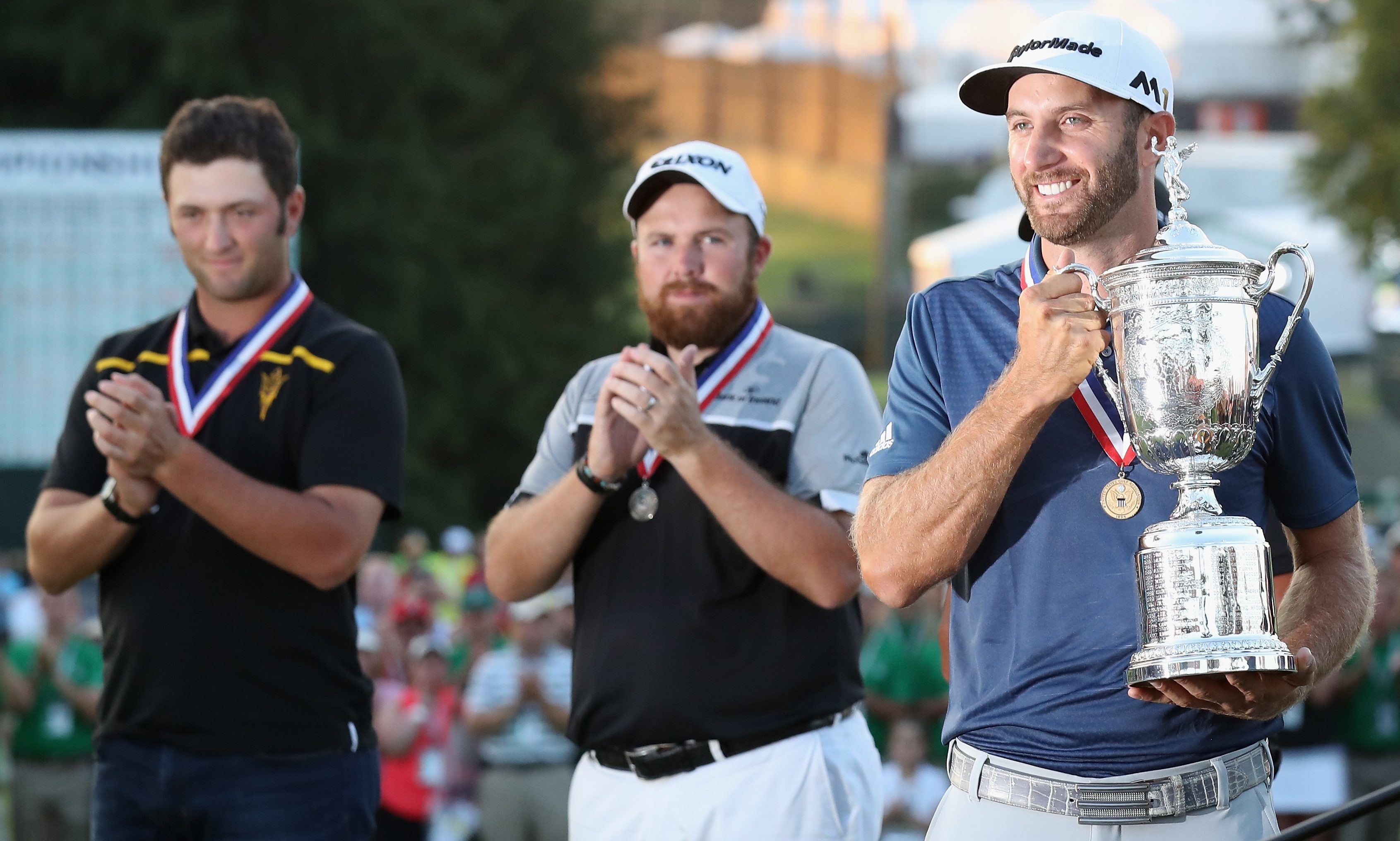 Shane Lowry watches on as Dustin Johnson lifts the winners trophy.