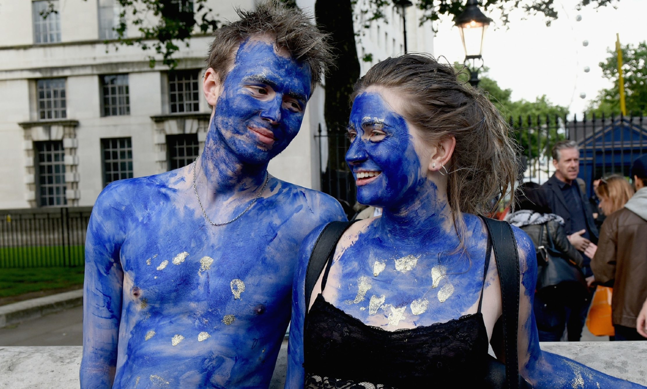 A young couple painted as EU flags protest outside Downing Street against the United Kingdom's decision to leave the EU.