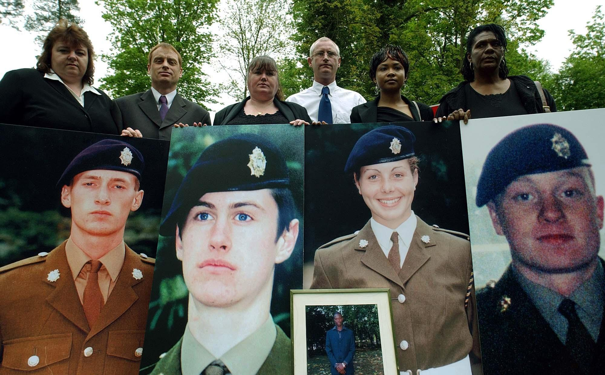 Yvonne Heath (formerly Collinson), Jim Collinson, Diane Gray, Geoff Gray, Deveen Clarke and Glasme Davis hold picture boards of soldiers who died while serving at Deepcut Barracks.