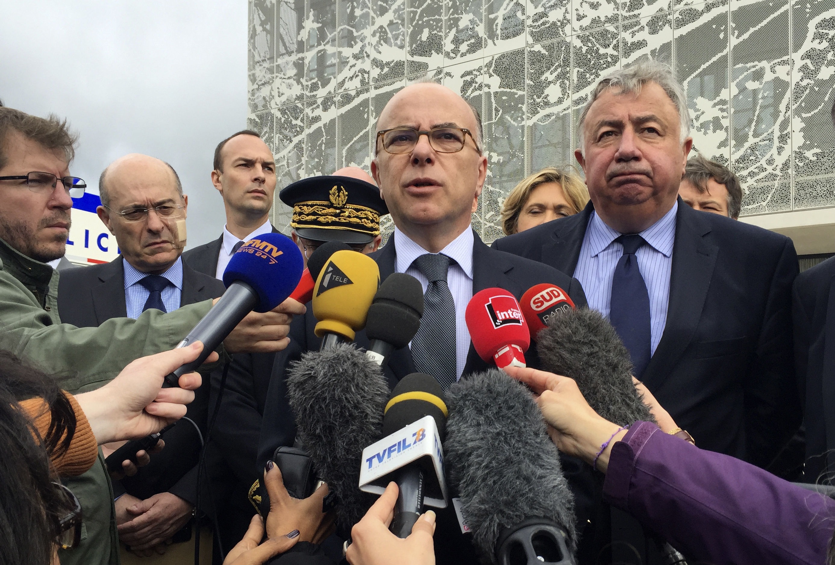 French Interior Minister Bernard Cazeneuve answers reporters after visiting the police station in Les Mureaux, west of Paris.