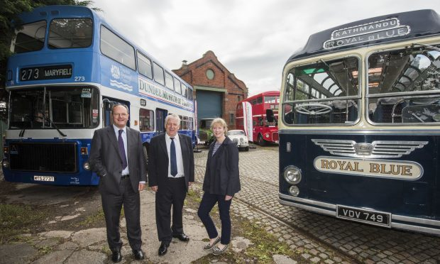 Jimmy McDonell, chairman of Dundee Museum of Transport, discussing the changes the funding will allow them to make with Martin Fairley, head of grants at HES, and MSP Shona Robison.