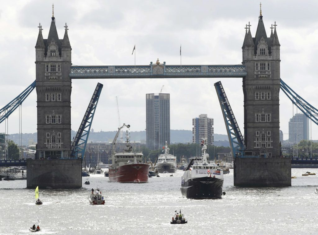 "A pro-Remain inflatable dinghy sails alongside a Fishing for Leave pro-Brexit ""flotilla"" making its way under Tower Bridge."