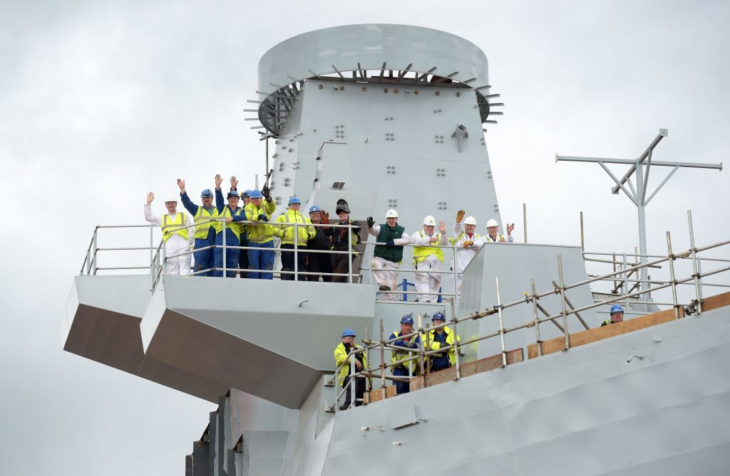 Workers wave during the tour by the Prince of Wales, known as the Duke of Rothesay when in Scotland,  of the aircraft carrier HMS Prince of Wales at Rosyth Dockyard, Rosyth. PRESS ASSOCIATION Photo. Picture date: Tuesday June 21, 2016. PRESS ASSOCIATION Photo. Picture date: Tuesday June 21, 2016. Photo credit should read: Jane Barlow/PA Wire.