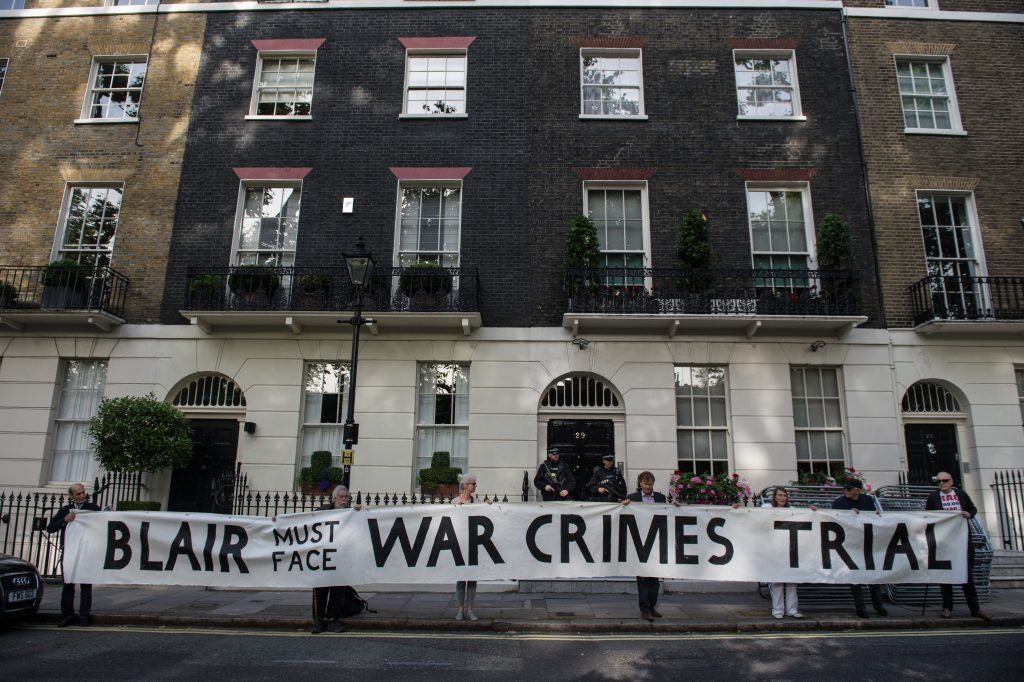 Protesters hold up a banner outside Tony Blair London residence on the morning of the Chilcot Report's release.