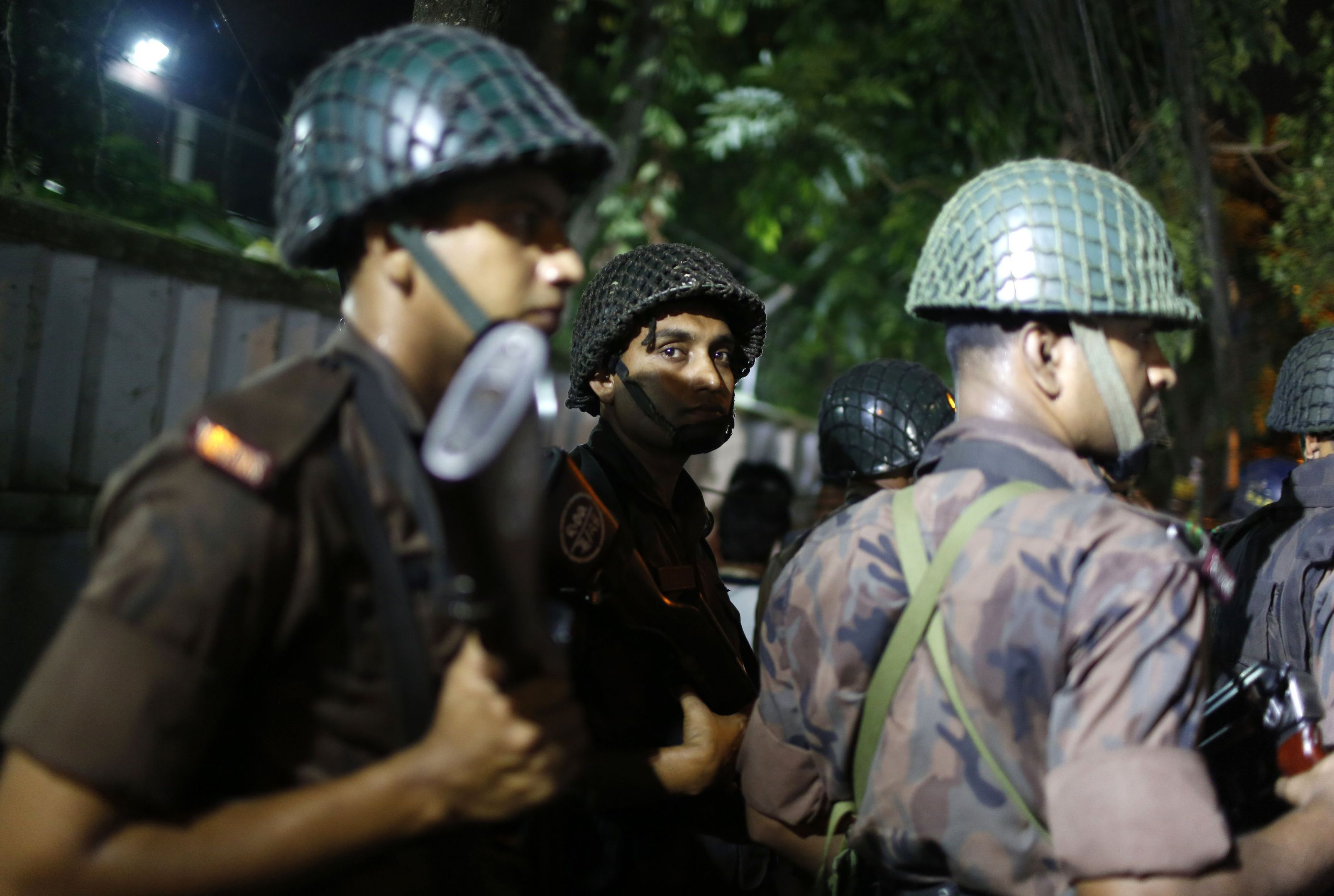 Bangladeshi security personnel stand guard near a restaurant that has reportedly been attacked by unidentified gunmen in Dhaka.