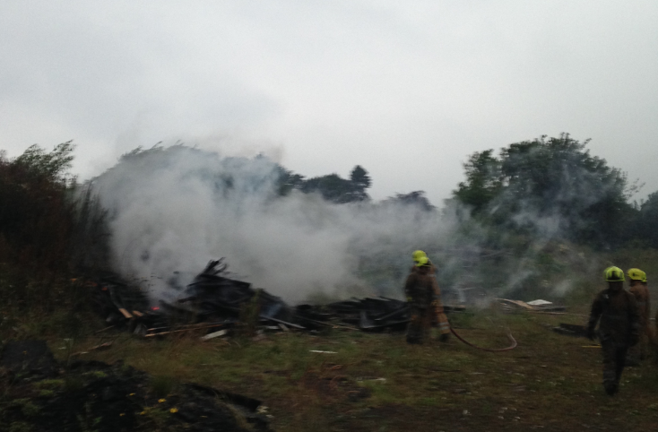 Fire fighters controlled the large wood fire, but are unclear as to how it began.