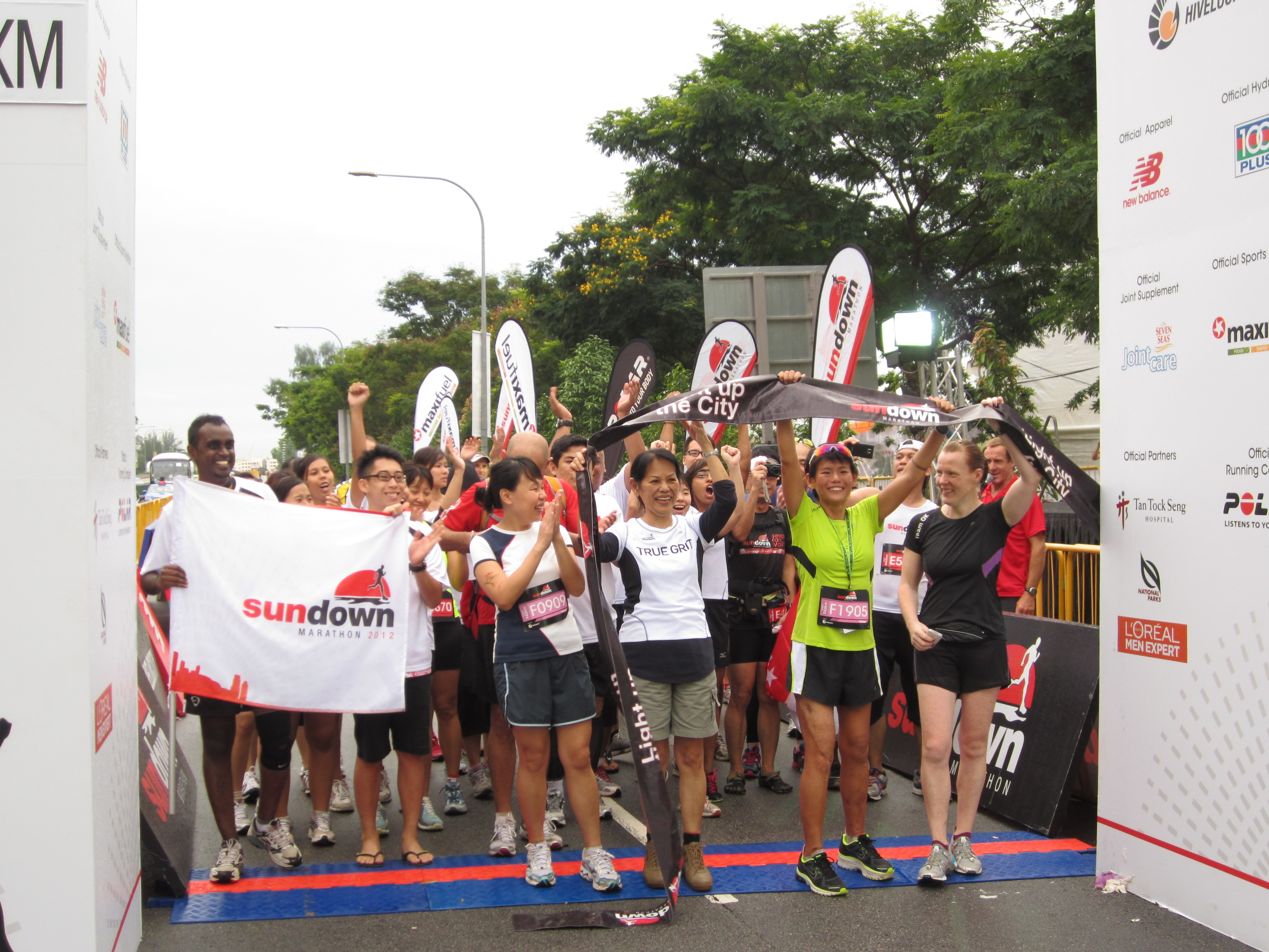 Kirsten (in green T-shirt, second right) and Orla (far right) celebrate the end of Kirsten's first 'race' after her accident: the Singapore Sundown Marathon in 2012, which took her 10 ½ hours to walk.