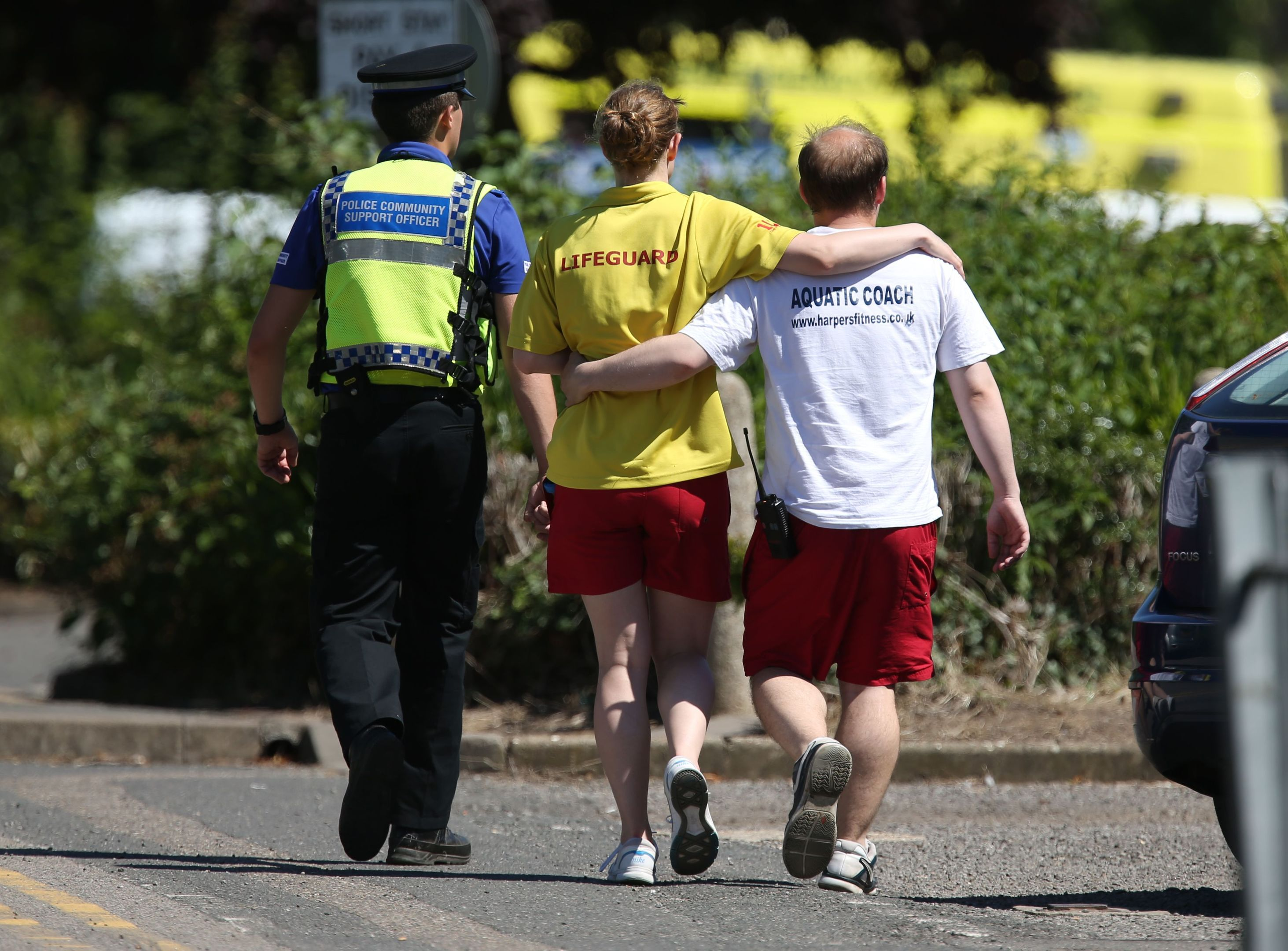 A lifeguard and swimming coach are escorted by a community support officer as they walk towards Castle Swimming Pool in Spalding, Lincolnshire, after three people including a suspected gunman have been shot dead.