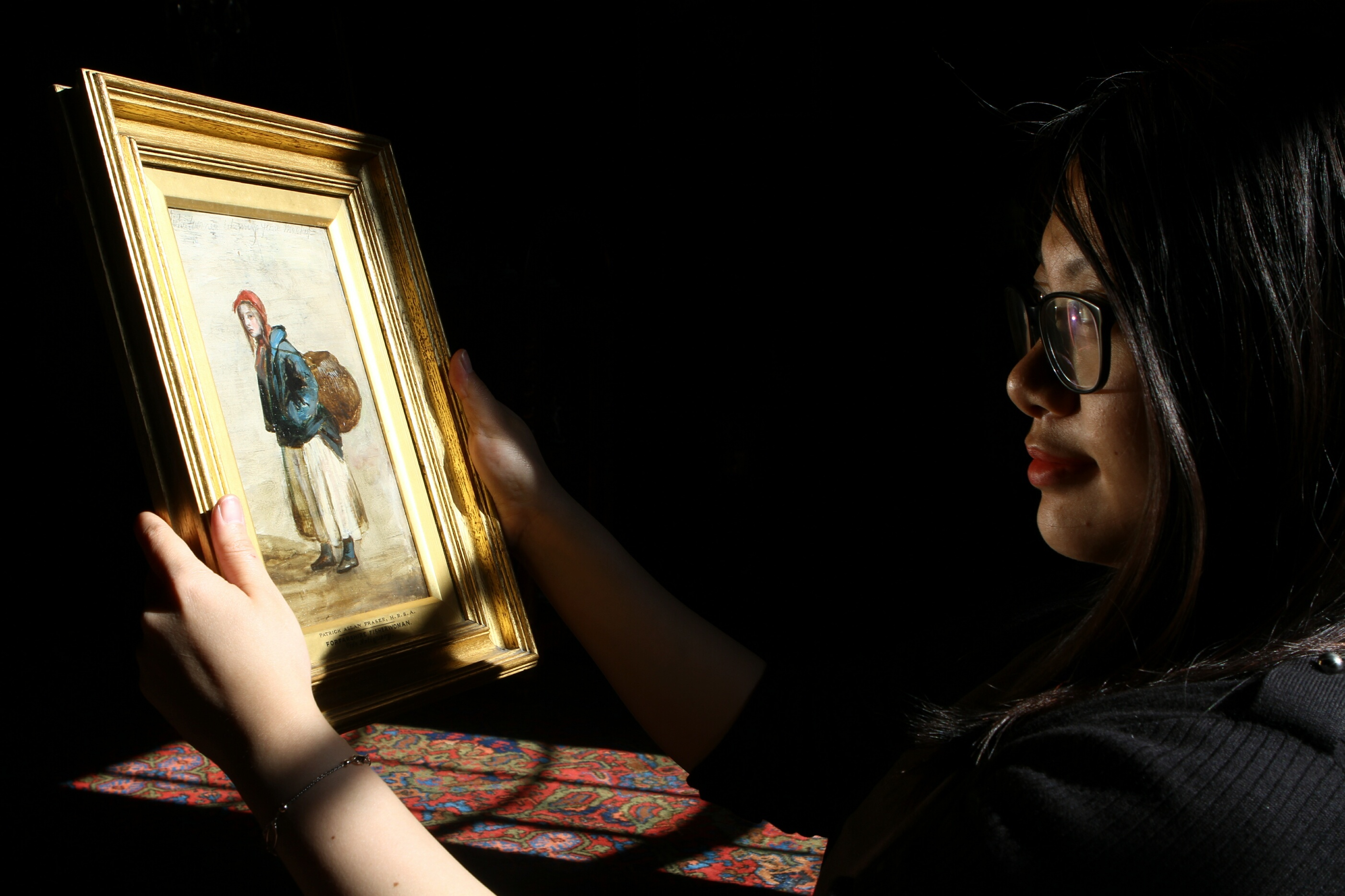Programme trainee Morgana Ho with one of the Patrick Allan Fraser paintings, Forfarshire Fisherwoman.