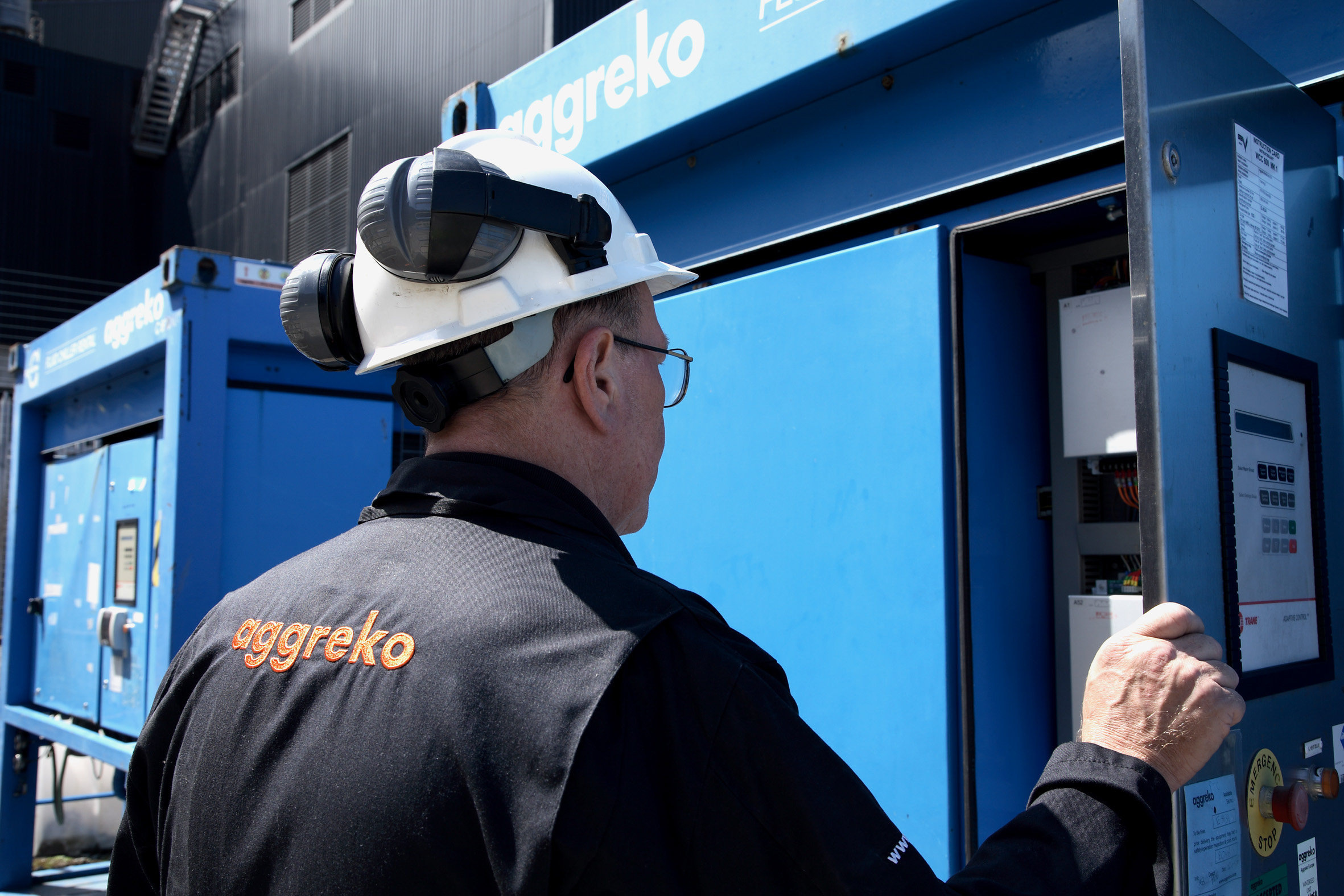 An Aggreko technician checks a power unit