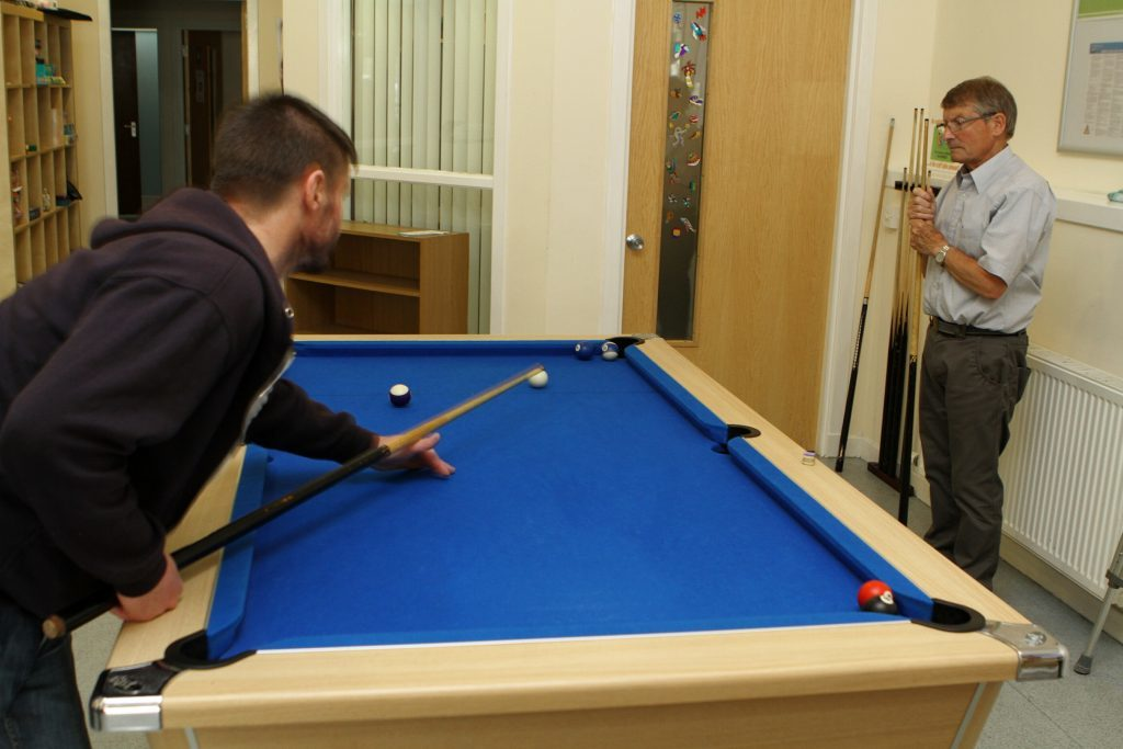 One of the service users having a game of pool at the Havilah Project in Arbroath.