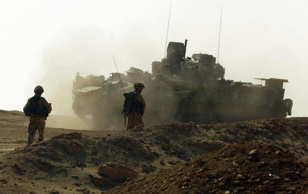 Soldiers from A company of the 1st Battalion Black Watch move back to their Warrior armoured vehicle in 2004 after community patrolling through the area of Ahmed Al Ahamadi near Camp Dogwood. Three Black watch soldier died in a suicide attack at a vehicle checkpoint the previous day.