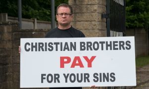 Dave Sharp protesting with a banner outside the Christian Brothers premises of Woodeaves, Wicker Lane, Hale Barns, Altrincham, Cheshire,  on Thursday  June 23 2016