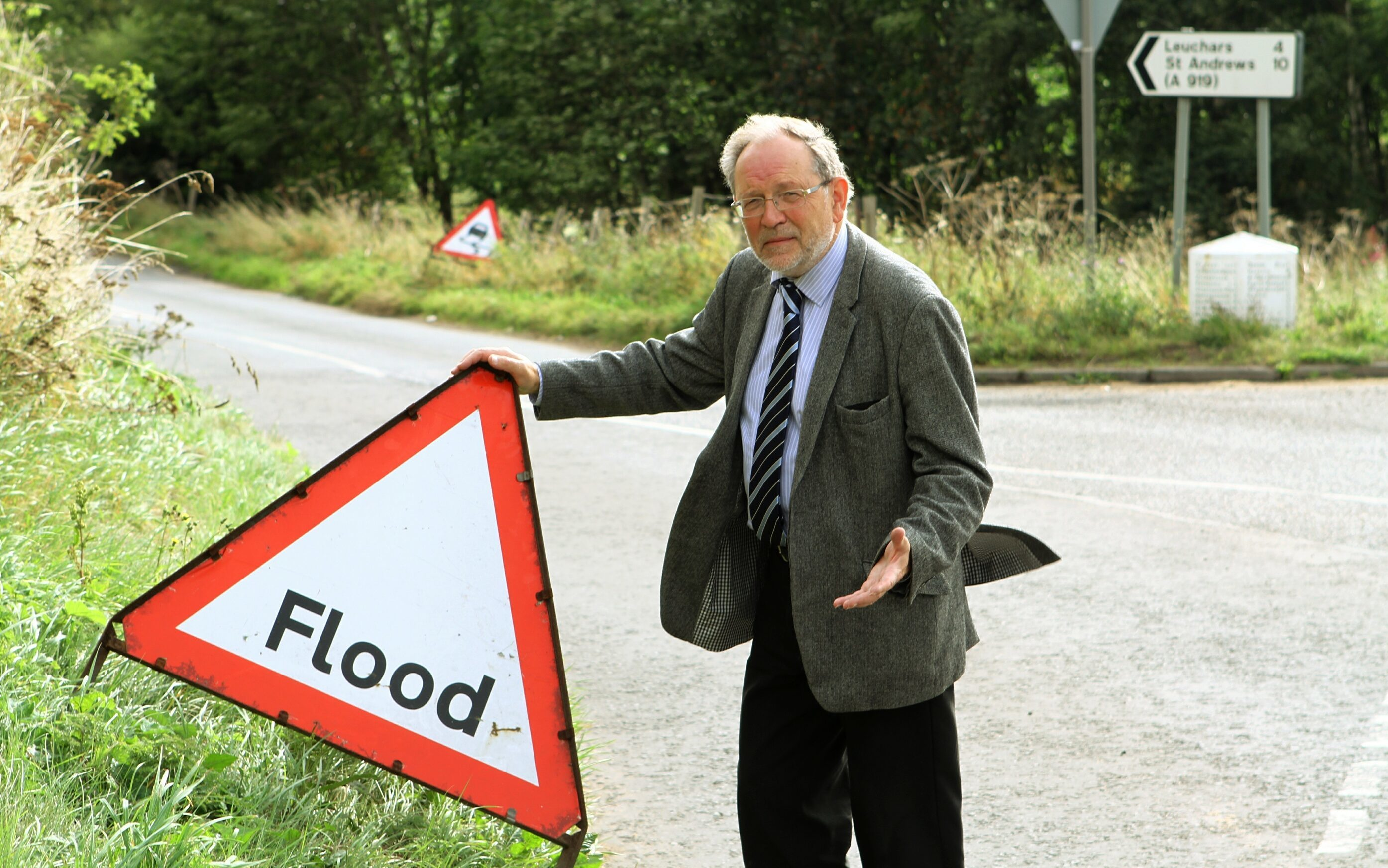 Tim Brett beside one of the leftover flood signs near Wormit