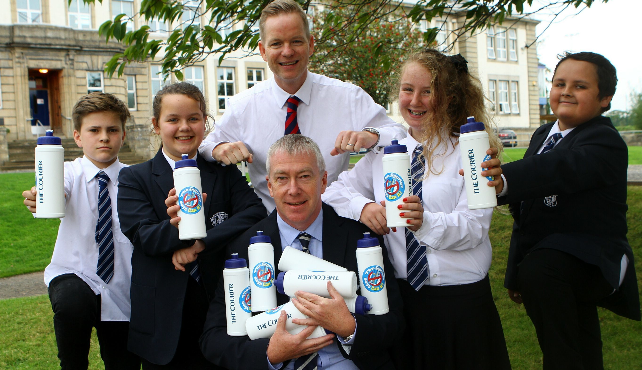 Richard Burdge of The Courier hands the bottles to head teacher Johnny Lothian and pupils
