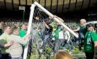 Hibs fans rush the pitch as they celebrate their side's historic win