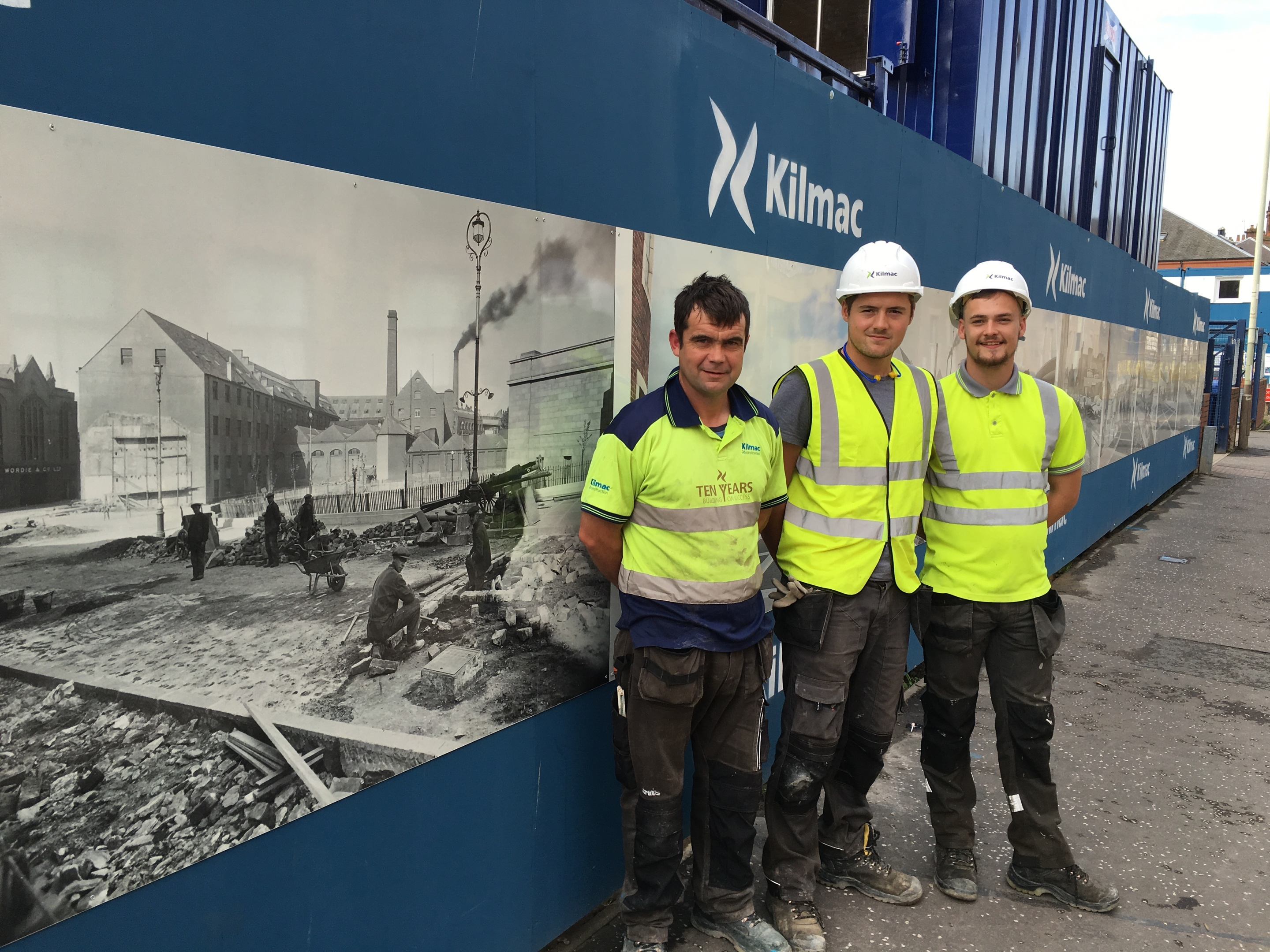 Kilmac foreman Derek Riddoch (left) with Rhys Davies and Dale Burns at the Mill Street hoarding.
