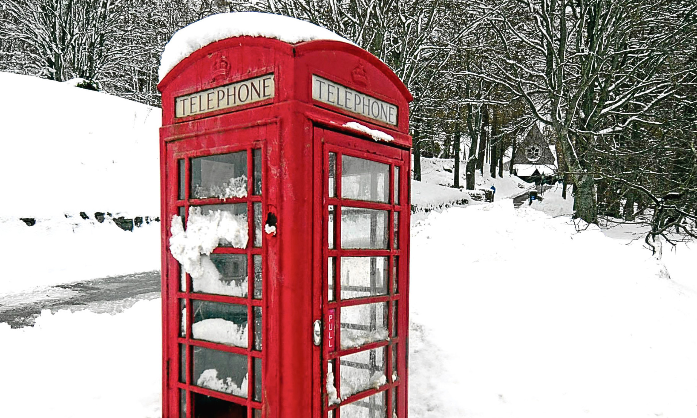 Out in the cold. A snow entrenched phonebox near the Balmoral estate, Aberdeenshire. Could it and many others be an endangered species?