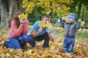 Young family with son playing in autumn park