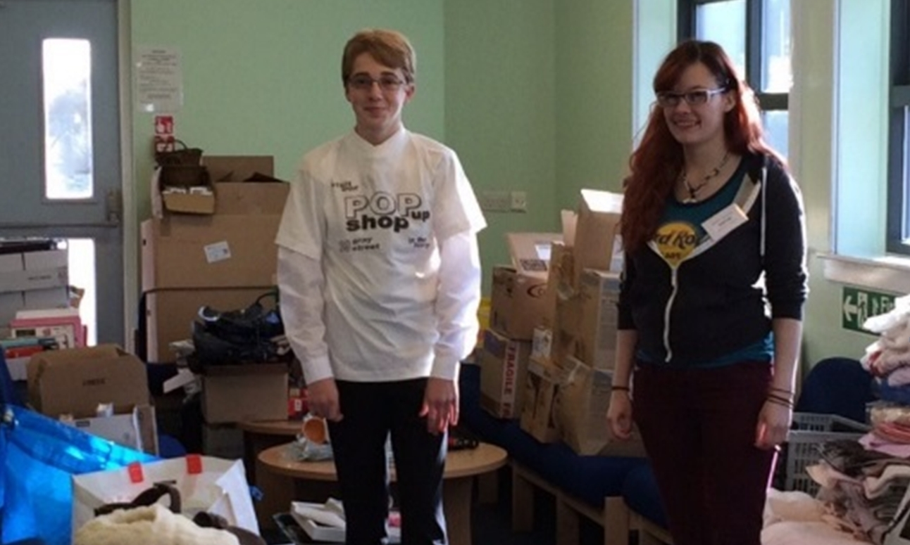 Pupils Samuel and Cora helping to sort the collection of donated goods.