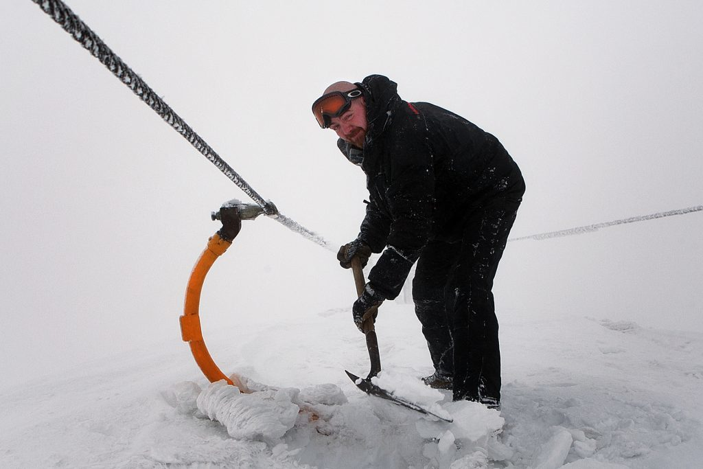 Glenshee, 2014. Graeme Davidson of the ski patrol tries to dig out a chairlift.