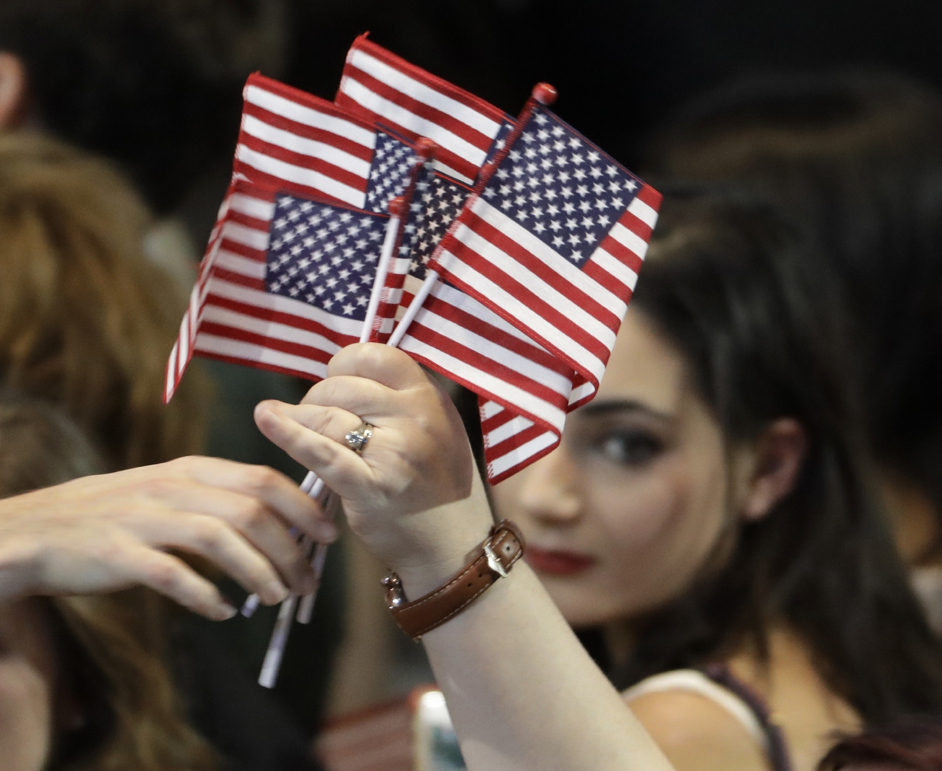 American flags are handed out at a rally.