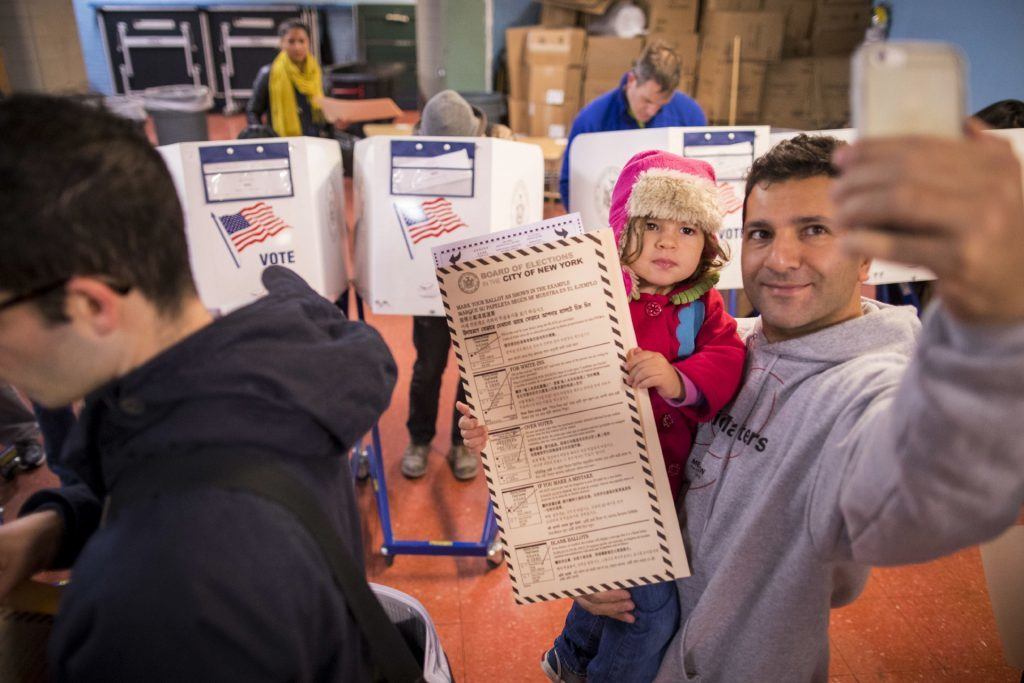 A man takes a selfie with his child as he waits to vote at a polling station in the Brooklyn borough of New York
