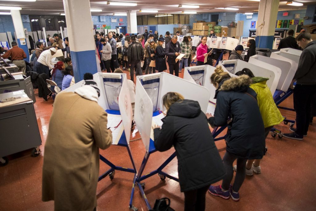 Voters fill out their forms and wait to vote at a polling station in the Brooklyn borough of New York