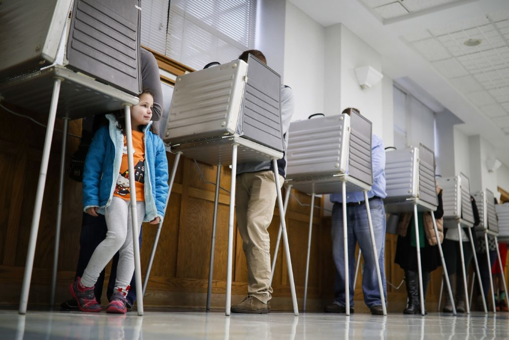 Violet Lay waits beside her mother Susan to finish voting in a polling booth at the Nativity School on Election Day, in Cincinnati.