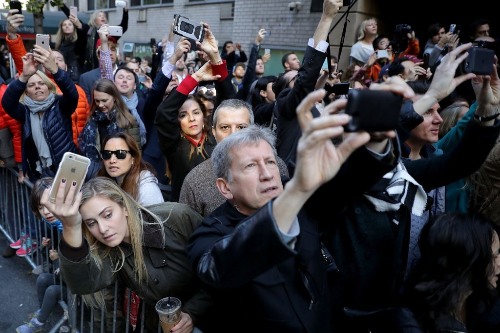 People gather along E 56th Street as they try to catch a glimpse or make a photograph of Republican presidential nominee Donald Trump after he voted on Election Day