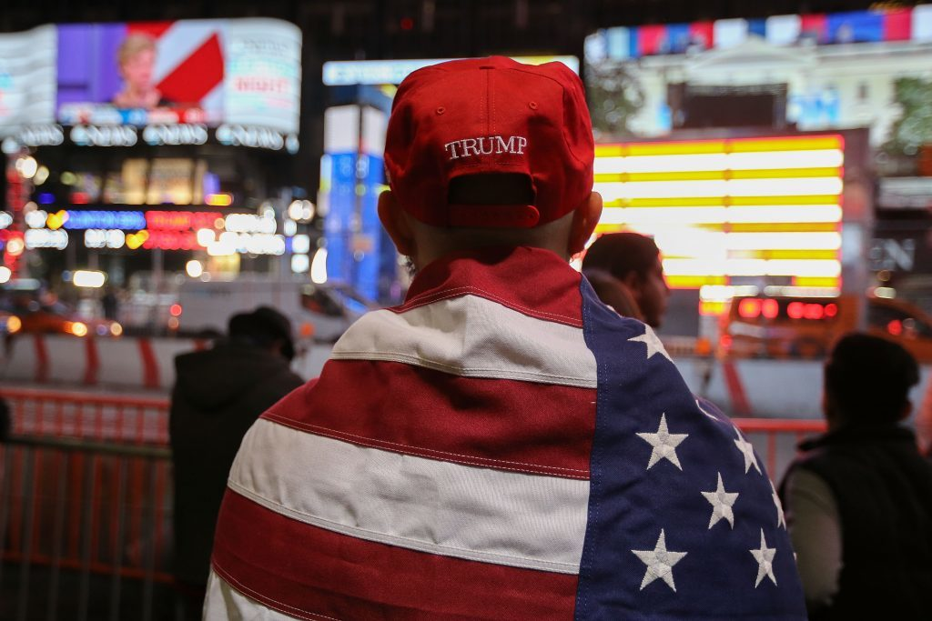A Donald Trump supporter watches the screens outside Times Square Studios as he awaits the results of the U.S. presidential election