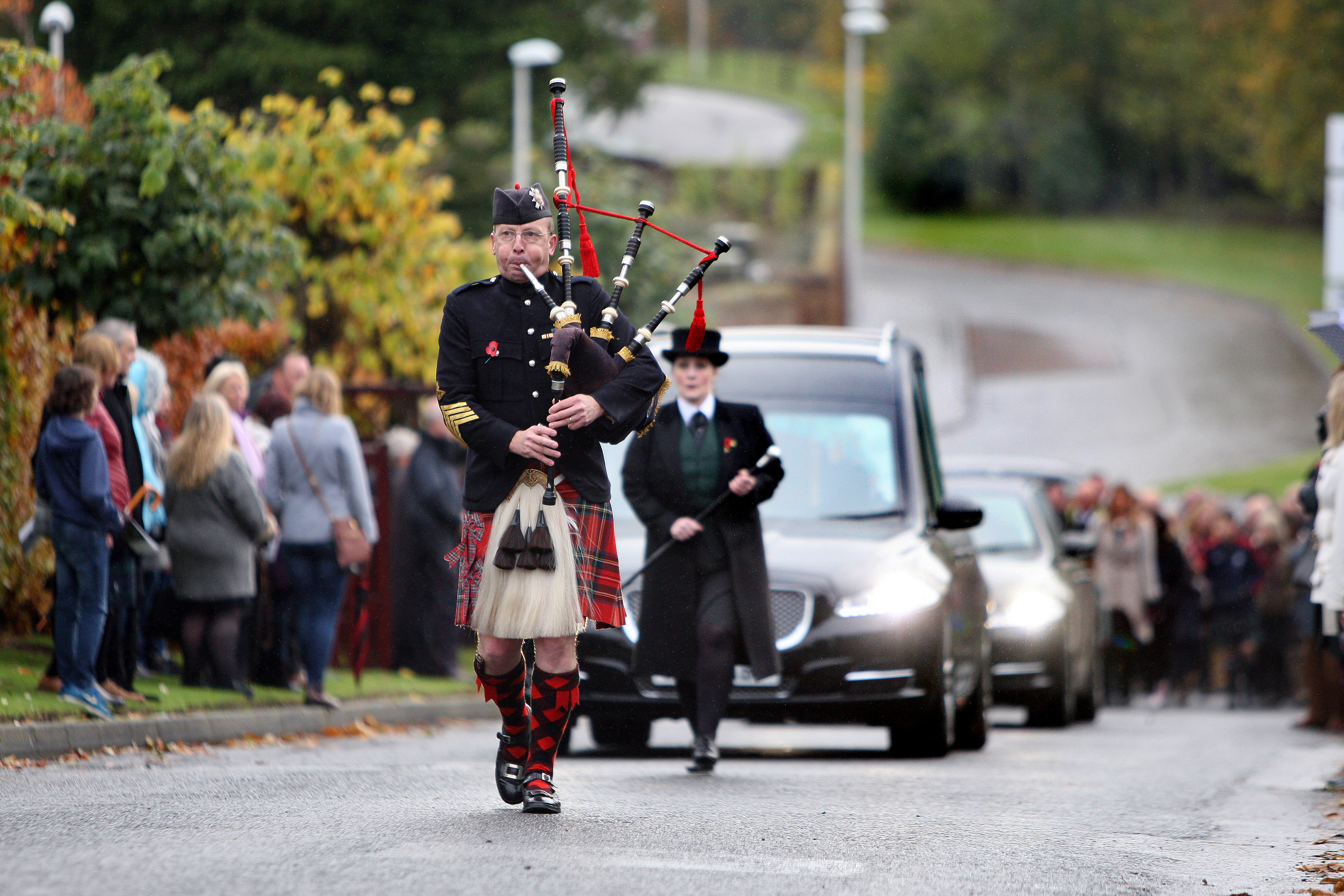A piper leads the hearse carrying Ewen Chisholm and followed by hundreds of mourners on way to Kirriemuir cemetery,