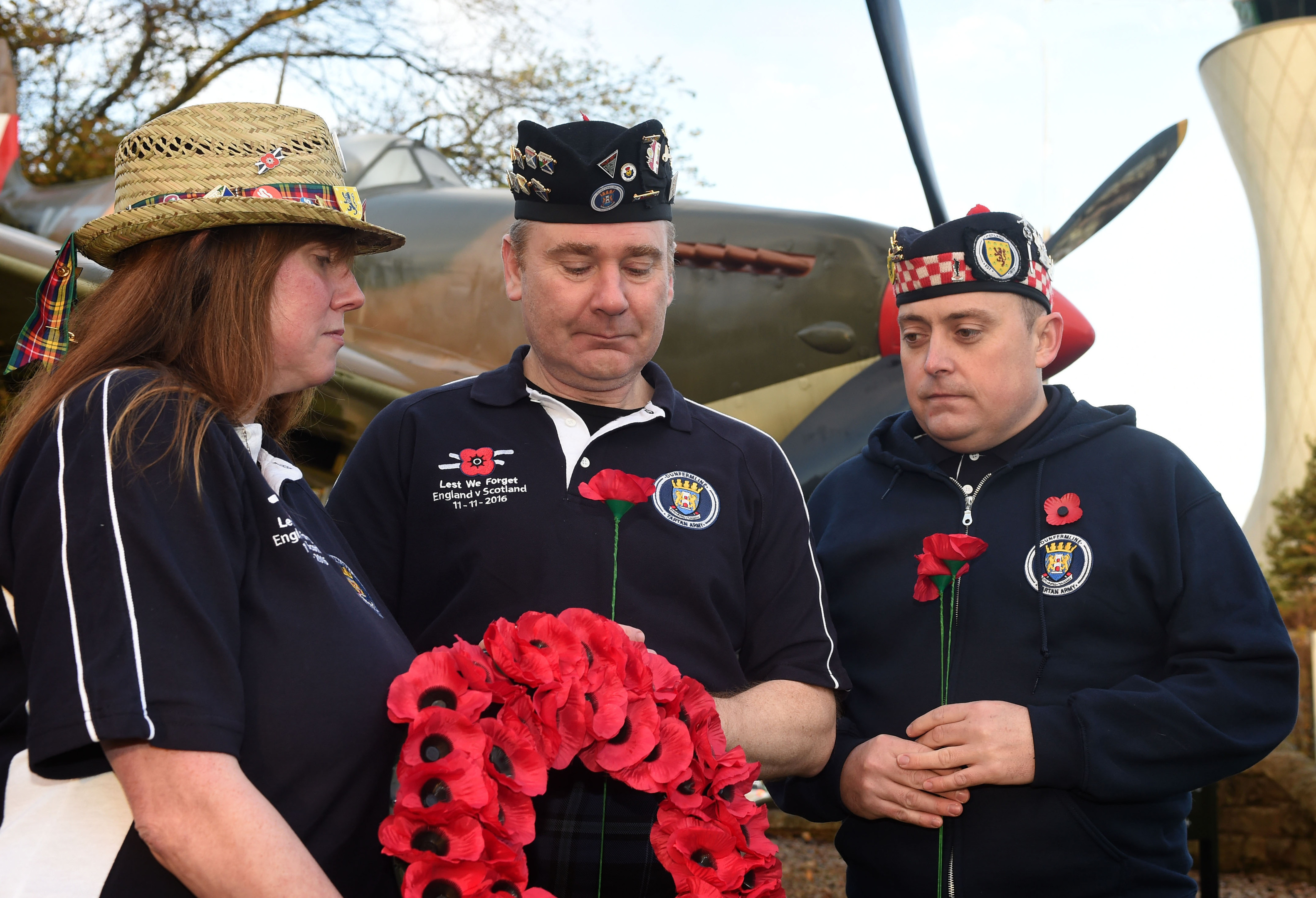 Members of the Tartan Army Jim and Audrey Ford, accompanied by Steven Avril pay their respects at the site of a WW 2 Spitfire at Edinburgh Airport.