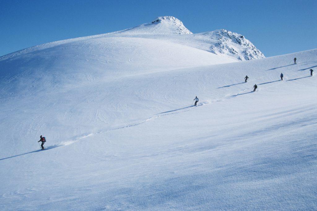 Skiers going downhill near Whistler, British Columbia.