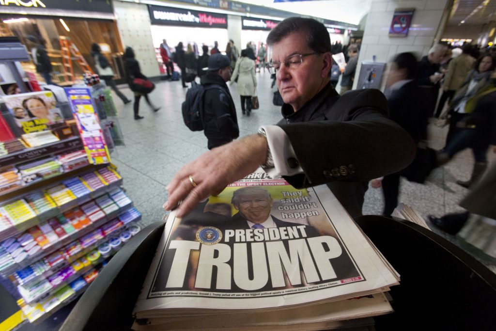 A man reaches for the New York Post newspaper featuring president-elect Donald Trump's victory,