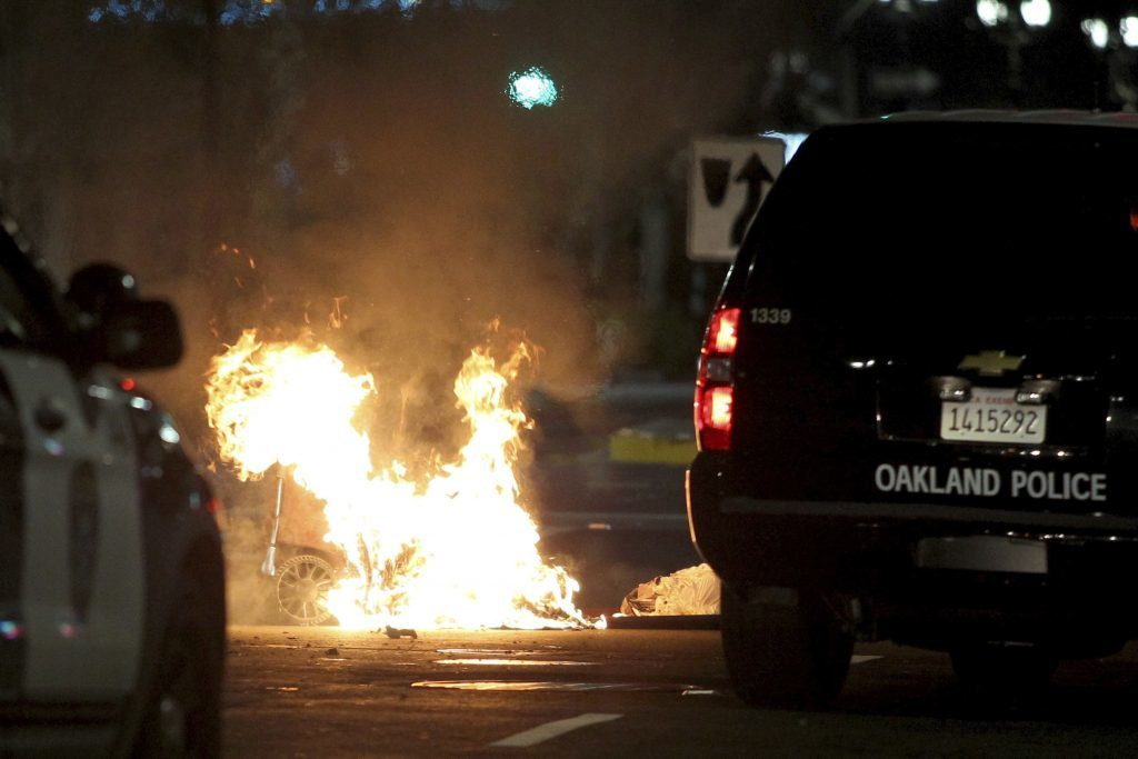 A trash fire burns during protests in Oakland, California