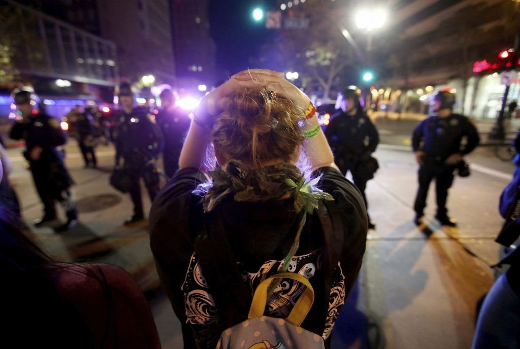 A protester faces a police line in downtown Oakland, California
