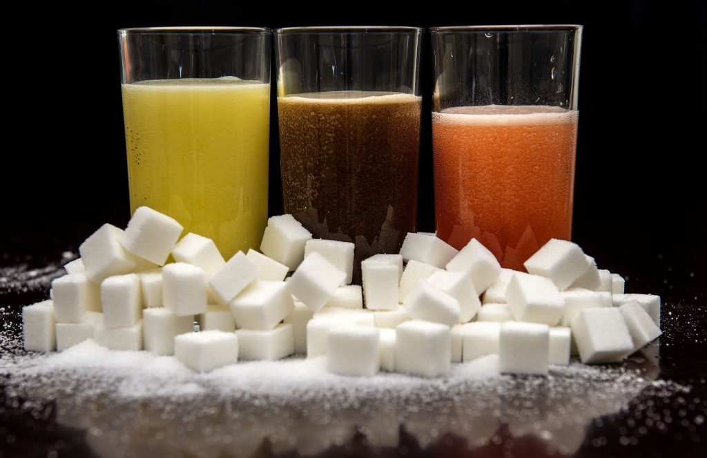 Carbonated drinks surrounded by sugar cubes,
