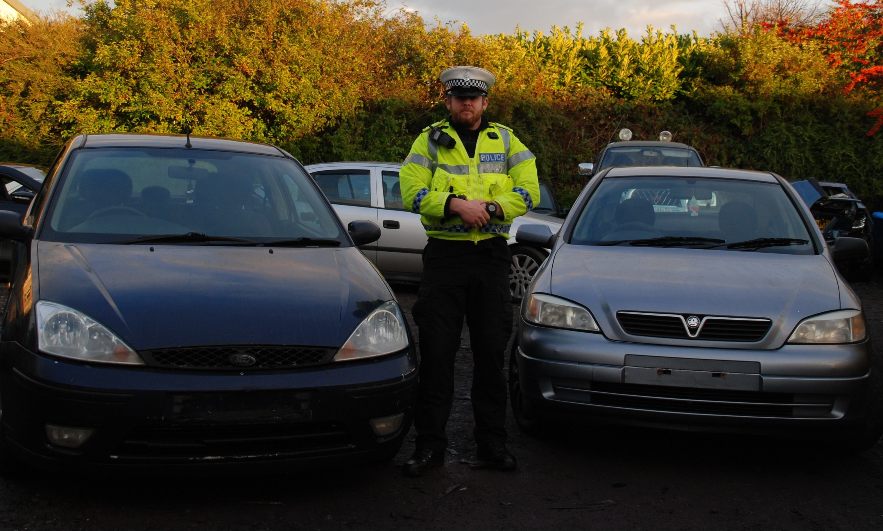 PC Chris McElwhee with two seized vehicles.