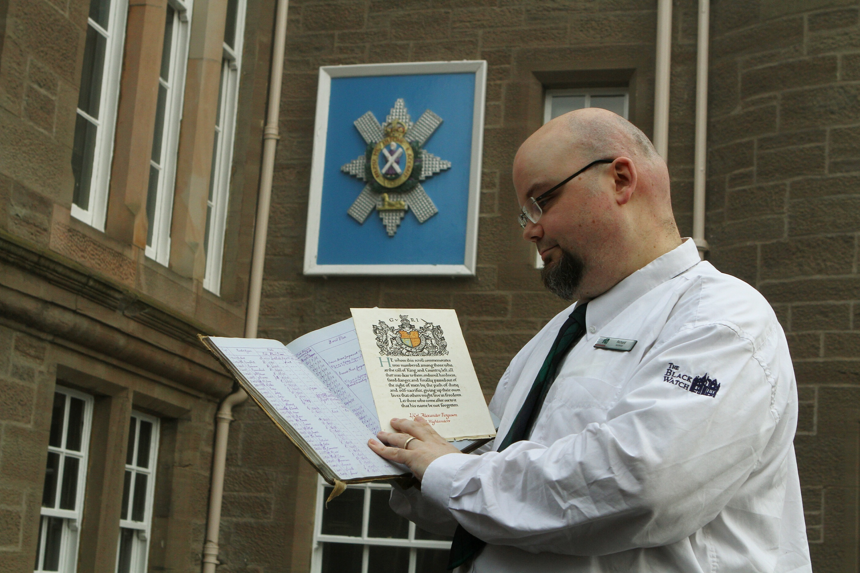 Richard McKenzie, Archivist at the Black Watch Museum, holding  the Burial Book of the 1st Battalion Black Watch and the Scroll Of Honour from L.Cpl. Alexander Ferguson of the Royal Highlanders.