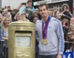 Andy murray stands next to his gold painted post box in Dunblane.