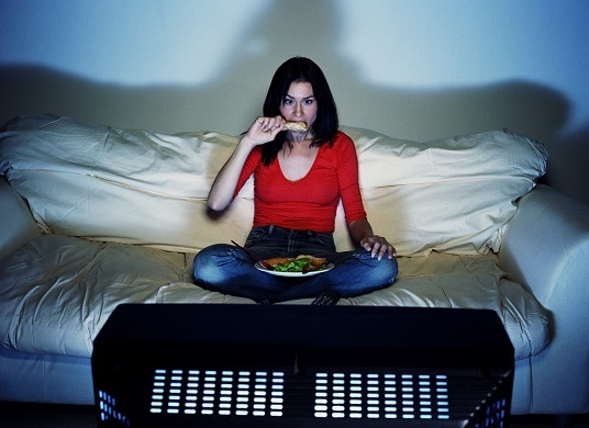 Young woman eating and watching television