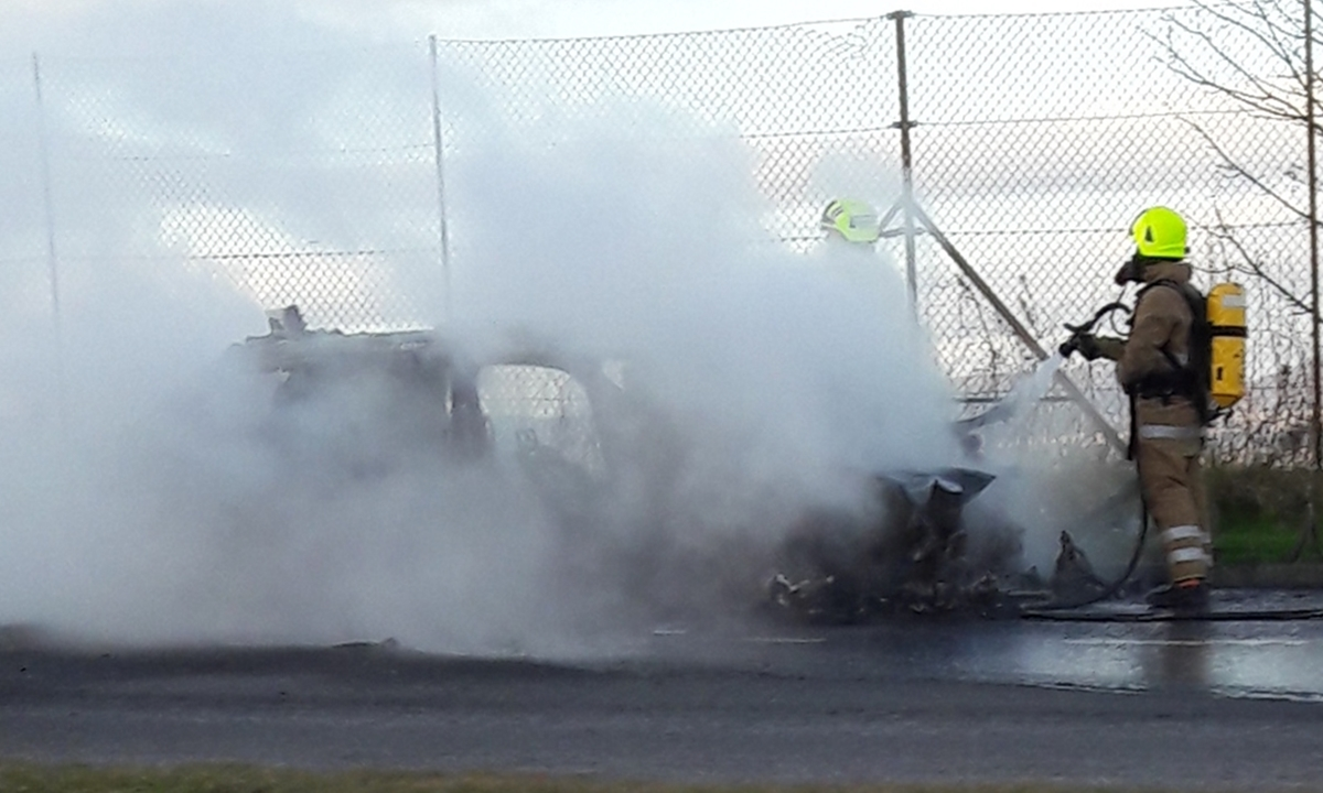 Firefighters tackle the blazing vehicle.