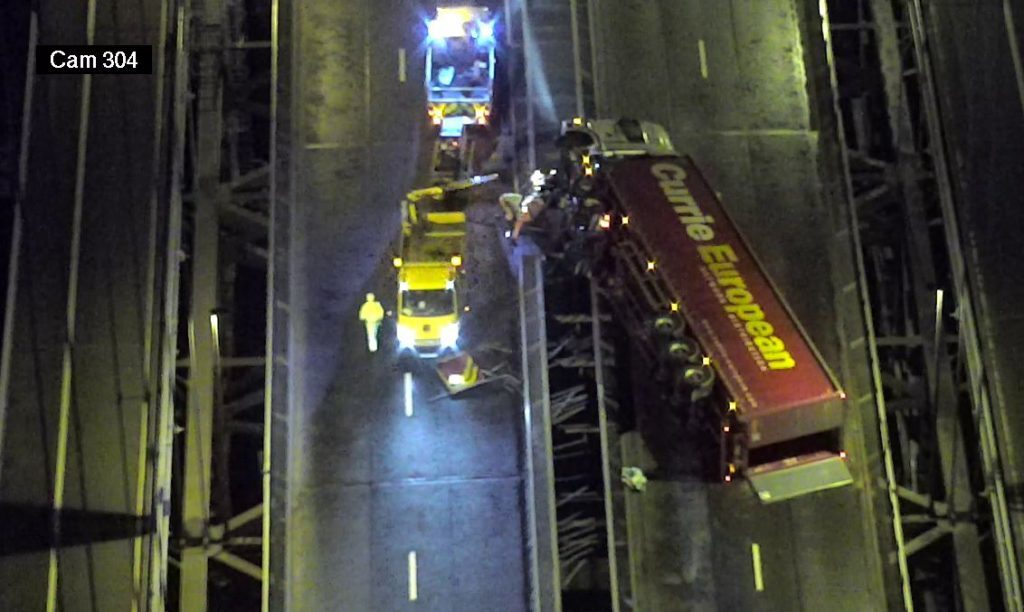 An overhead camera shows the toppled lorry.