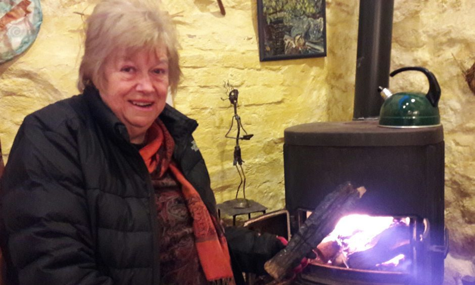 Marianna Lines adds an ember from the traditional Burning of the Clavie to her fire