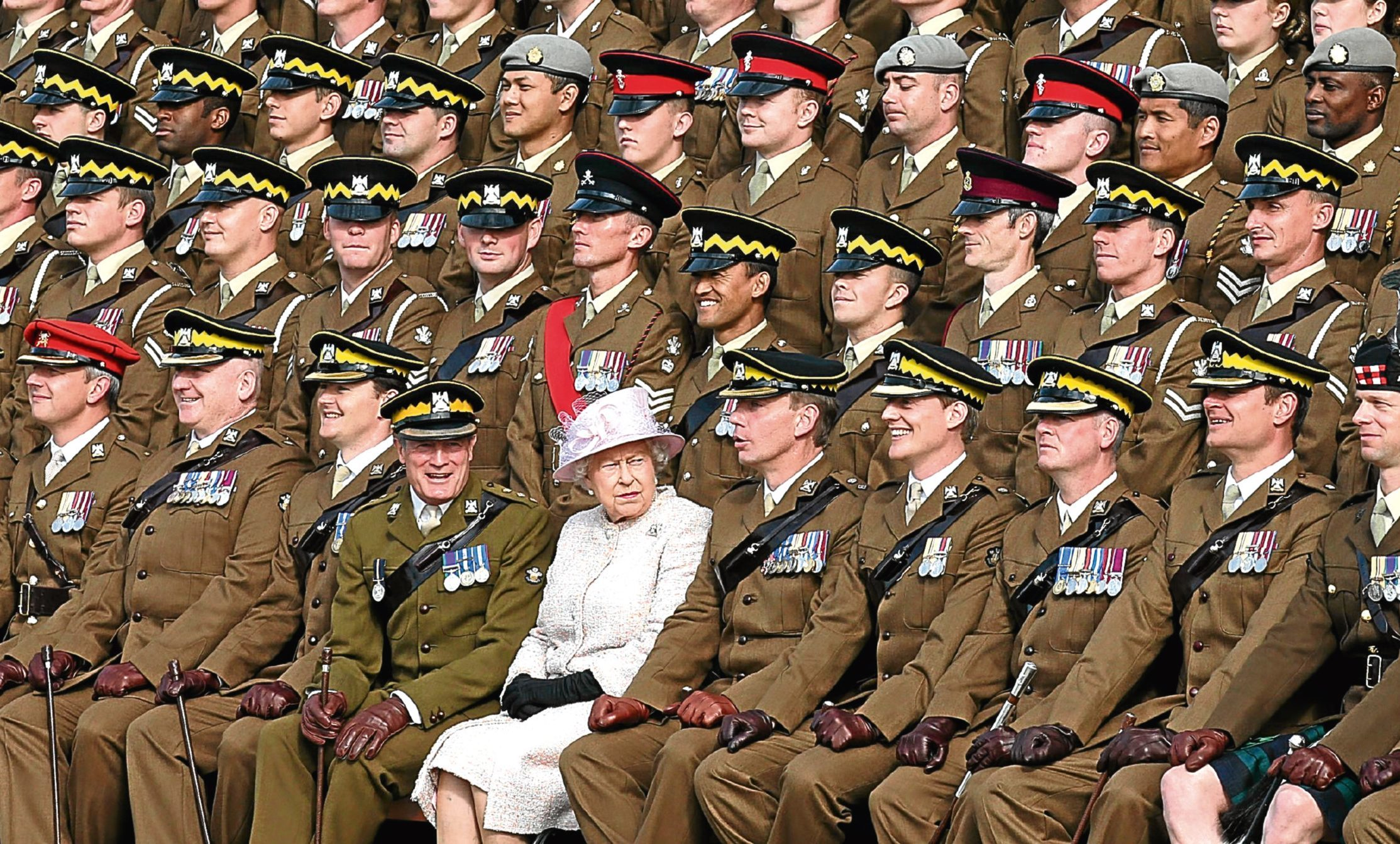 The Queen joins soldiers for a regimental photograph during a visit to the Royal Scots Dragoon Guards at the regiment's new barracks in Leuchars.